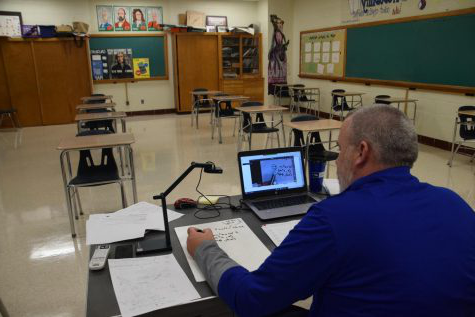 Math teacher Mr. Budrow teaches with his document camera as he works through a problem with students.